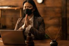 Online Prayer. Church Service. Asian Woman Praying Wood Table, Laptop. Buddha. Spiritual. Buddhism. Meditation. Camera Focus On Buddha Figure