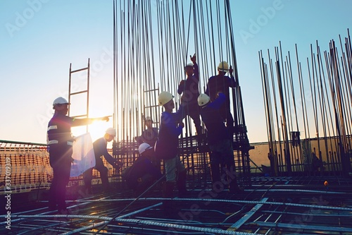 Fotografering The construction of a rooftop high rise building, workers are tied with steel bars for concrete pouring, surveying the site and cranes are lifting or moving metal at the construction site