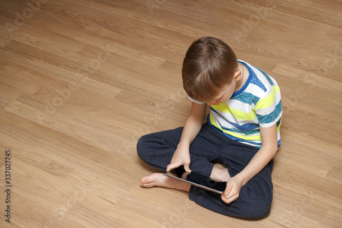 Fototapeta Modern generation. The child plays games or watches cartoons. A boy is playing with his tablet. obraz na płótnie