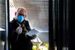 canvas print picture - Un hombre con mascarilla levanta su dedo pulgar en señal de éxito contra el Coronavirus mientras trabaja con una Tablet, confinado en el balcón de su casa