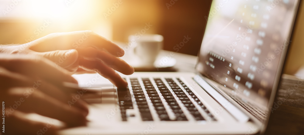 Fototapeta Close-up photo of male hands with laptop. Man is working remotely at home