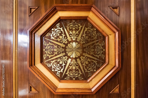 Carved wood door inlaid with gold Fototapeta