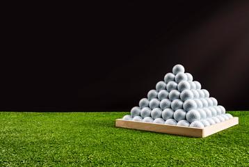 Pyramid of golf balls in a driving range, black background, horizontal image