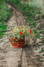 A Basket Of Wildflowers Stands On The Road. Vertical Frame.