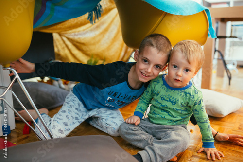 Fototapeta brothers playing in their built indoor fort in living room