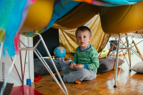Fototapeta little boy playing in his built indoor fort in living room