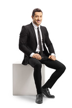 Young Businessman Sitting On A White Cube And Looking At Camera