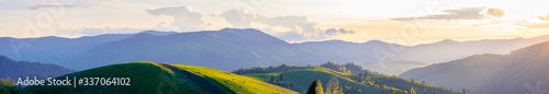 Obraz panorama of mountainous countryside in springtime at dusk. path through rolling hills. ridge in the distance. clouds on the sky. beautiful rural landscape of carpathians - fototapety do salonu