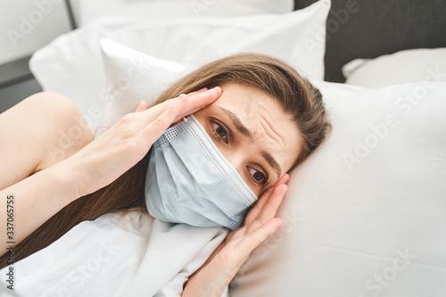 Girl with a splitting headache lying in bed Wallpaper Mural