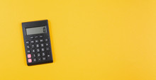 Top View Of Pocket Calculator On Orange Background, Business Calculation And Finance Concept