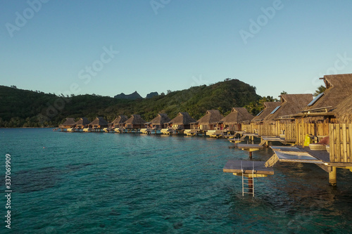 Carta da parati Overwater Bungalows over Turquoise Lagoon with Reef at Sunset in Bora Bora Frenc