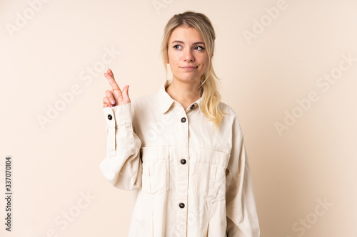 Blonde woman over isolated background with fingers crossing and wishing the best Wallpaper Mural