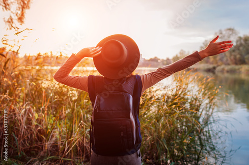 Carta da parati Traveler with backpack relaxing by spring river at sunset