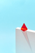 Red Plastic Pyramid On White Box With Shadow Around Blue Background With Copy Space.
