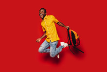 Cheerful Young Black Man Jumping With A Backpack
