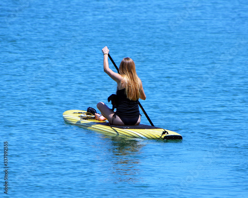 Photo Attractive blonde woman and her pet dog on a ;addle board.
