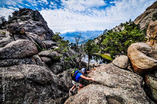 Fototapeta man scrambling on rock cliff