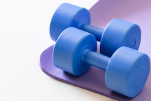 Sports Ware For Gym. Sport Concept. Sporting Items On Purple Background Or Lavender. Blue Dumbbell On Purple Mat Sport. Space For Your Text. Sports Concept. Sport Equipment. Fitness