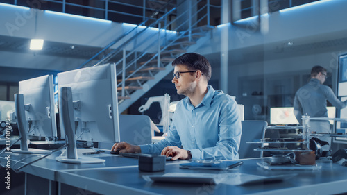 Foto Electronics Development Engineer Sitting at His Desk Uses personal Computer for Programming