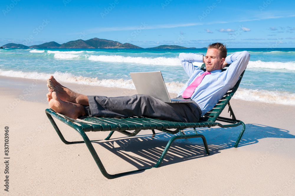 Fototapeta Barefoot businessman working on his laptop on a beach chair relaxing on the shore of an empty tropical beach