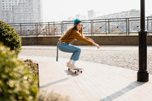 Skateboarding At City. Female,...