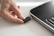 A Man Plugs A USB Flash Drive Into A Laptop With His Hand