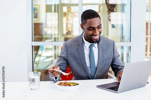 Fototapeta Portrait of a happy smiling young man in business suit eating lunch at work at his desk while working  on laptop computer in his office obraz