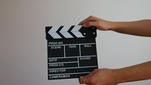 Close Up Female Hold In Hand Wooden Black Clapperboard Isolated On Gray Background. Cinematography Production Concept. Copy Space Advertising Mock Up.