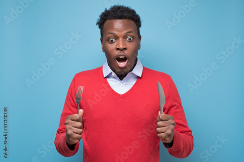 hungry young african american man with a knife and a fork is shocked with tasty meal Canvas Print