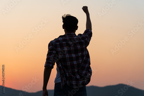 Fototapeta Man with fist in the air during sunset sunrise mountain in background