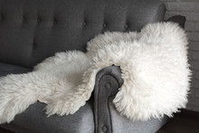 White Sheep Skin On A Gray Sofa. A Cozy Place To Relax In The Apartment