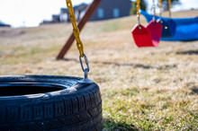 Low Angle View Of Tire Swing With Grass And Swings In Background