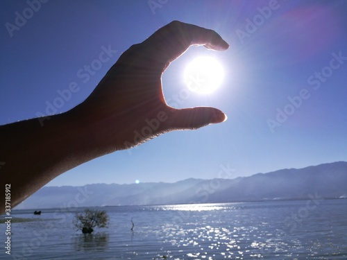 Naklejka premium Optical Illusion Of Man Holding Sun Over Sea Against Sky