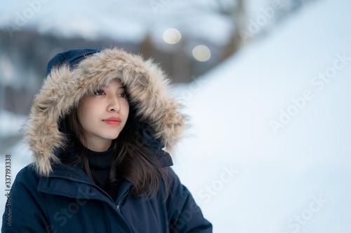 Obraz na plátne Portrait of woman wearing warm coat with fur hood, having fun in winter
