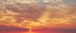 orange and gray clouds beautiful sunset ambiance with large yellow and orange sun in he sky surface hills.