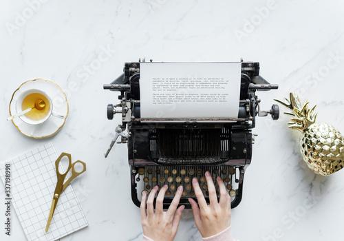 Fototapeta Aerial view of woman typing on a retro typewriter obraz