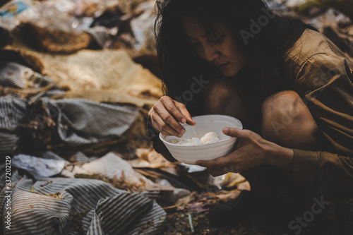 Fototapeta poor people or beggar begging you for help sitting at dirty slum