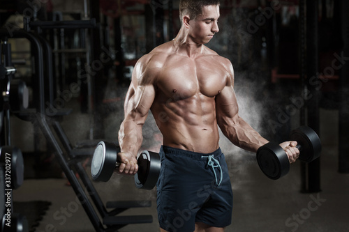 Athlete muscular bodybuilder in gym training biceps with dumbbell Fototapet
