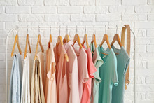 Rack With Hanging Clothes Near Brick Wall