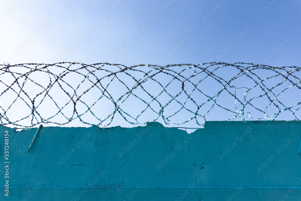 Fototapeta Stone wall with barbed wire against blue sky
