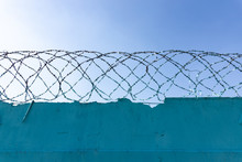 Stone Wall With Barbed Wire Against Blue Sky