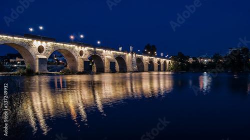 Illuminated Bridge Over Water In City At Night