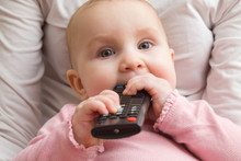 Infant Sitting In Mother Lap And Chewing Remote Control. Closeup. Front View. Favourite Baby Thing.