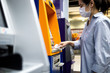 canvas print picture - Asian woman at the cash machine withdraw money,girl is using tissue paper to press the ATM keyboard instead of the finger,avoid infection,during the Coronavirus outbreak,contagious disease of Covid-19