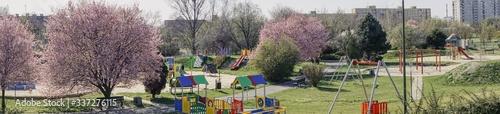 Obraz wiosenna panorama z placem zabawa dla dzieci, kwitnące drzewa i krzewy, przyrządy do zabaw i ćwiczeń, pusty plac w okresie pandemii - fototapety do salonu