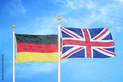Germany and United Kingdom two flags on flagpoles and blue cloudy sky Canvas Print