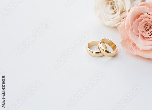 Leinwand Poster Golden wedding rings and two roses in soft tones on white background
