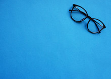 Classic Glasses With A Black Rim On A Blue Background