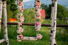 Wedding Swing Decorated With Flowers Hanging On The Branches
