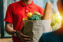 Handsome Food Delivery Service Man In Red Shirt Holding Fresh Food Set Bag To Customer At Door Home, Express Delivery, Quarantine, Virus Outbreak, Takeaway Food Delivery And Online Shopping Concept